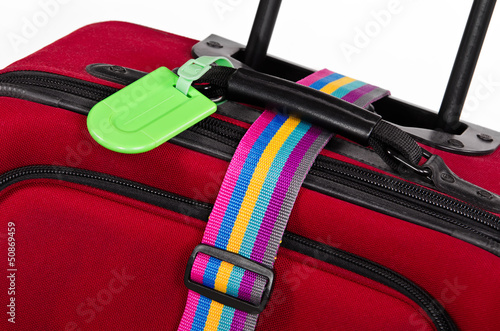 Green luggage tag and colorful belt on red suitcase