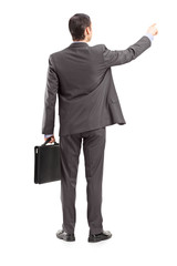 Full length portrait of a businessman pointing in a direction, s