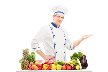 Male chef in a uniform gesturing with hand and posing behind a t