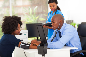 african medical doctor monitoring patient's blood pressure