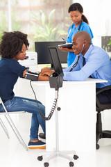 african doctor measuring patient's blood pressure