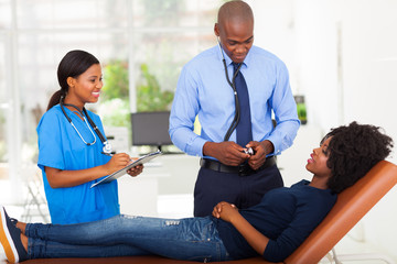 female african patient lying on doctor's examining couch