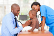 male pediatric doctor examining baby boy with female nurse