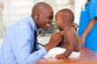 happy african male doctor examining baby boy