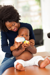 african mother feeding her son in doctor's office