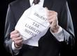 Businessman holding crumpled tax liability notice