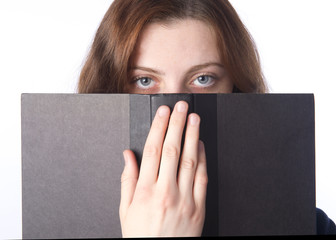 Young woman peers over book