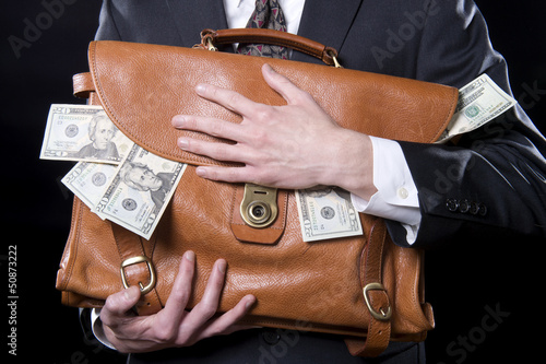 Closeup of man holding briefcase with money spilling out