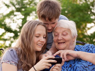 Young and old woman examine the image in phone