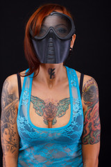 redhead woman with tattooed body in big black mask