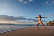 Woman in Warrior yoga pose on tropical beach
