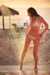 Beautiful woman taking shower on sunset beach