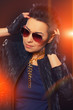 Beautiful woman in sunglasses with orange lights