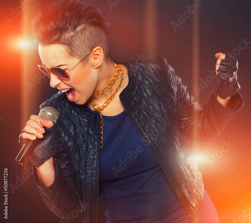 Hot rocker is singing in microphone