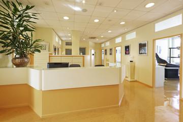 Empfangsbereich Zahnarztpraxis mit Zahnarztstuhl im Hintergrund