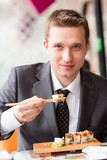 Young handsome businessman eating sushi with sticks