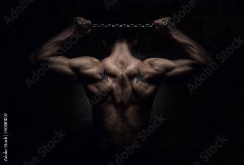 Muscular sports man stretching out over dark background