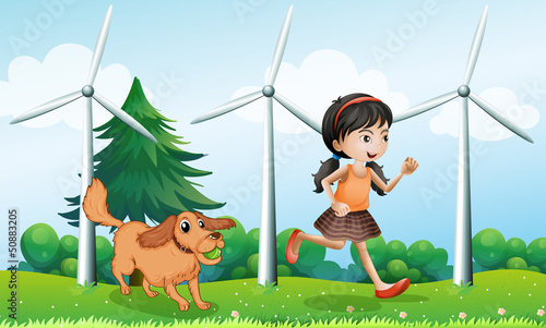 Fotobehang Honden A girl playing with her dog near the windmills