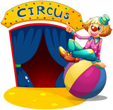 A clown sitting at the top of a ball pointing the circus house