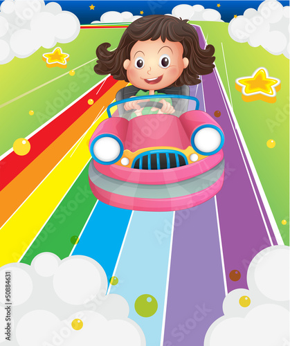 A little girl riding in a pink car