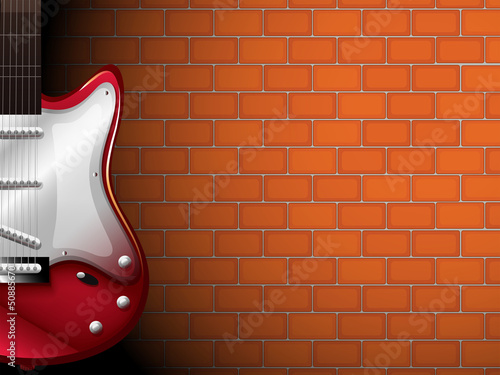 A guitar in front of a brick wall