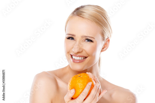 Smiling girl is holding fresh orange