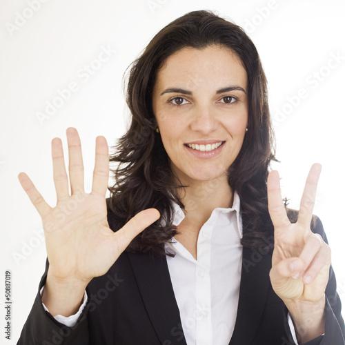 Frau zeigt mit sechs Fingern die Zahl 7 an