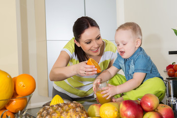 Mother and child making fresh orange juice - healthy life