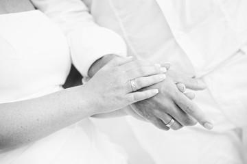 monotone shot of couple holding hands wear rings on sand