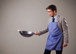 Young man holding a black frying pan