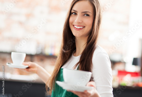 Waitress holding cups of coffee in cafe