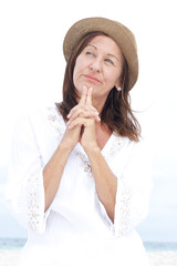 Thoughtful mature woman happy praying outdoor