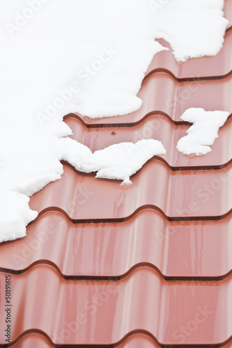 Melting snow on the roof with a metal roof