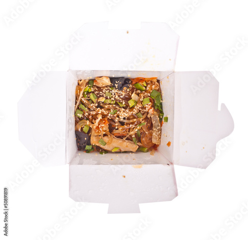 Noodles with pork and vegetables in take-out box on white backgr