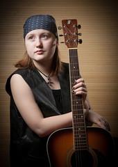 Девочка с гитарой в бондане кожаной жилетке