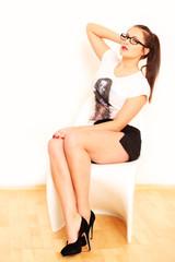 attraktives Mädchen sitzt auf weißem Stuhl