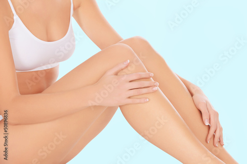 Beautiful woman's legs and hands isolated on white background