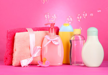 Baby cosmetics and towels on pink background