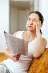 serious and wistful  woman with newspaper