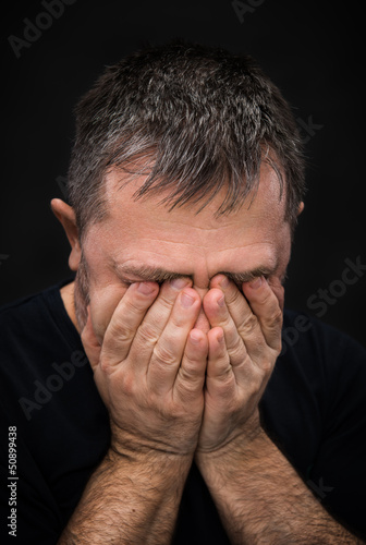 Despair. Man with face closed by hand