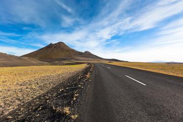 Highway through gravel lava field landscape under a blue summer