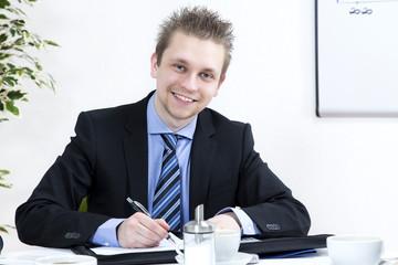 Junger Geschäftsmann mit Kugelschreiber in der Hand