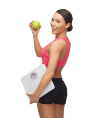 sporty woman with scale and green apple