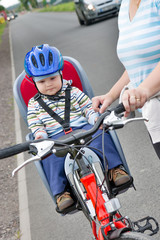 little boy with blue helmet on bicycle with mother