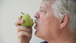 profile view of senior man eating a pear