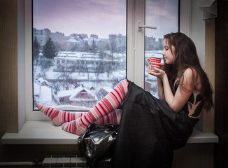 cute girl sitting on the windowsill