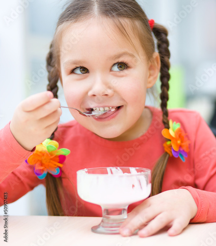 Little girl is eating ice-cream in parlor