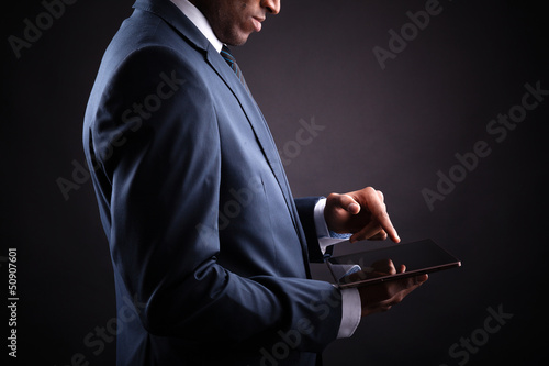 Businessman working on a digital tablet against black backgroun