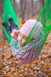 A girl lies in green hammock in the autumn forest