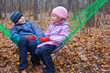 Brother and sister sitting together in hammock in autumn forest